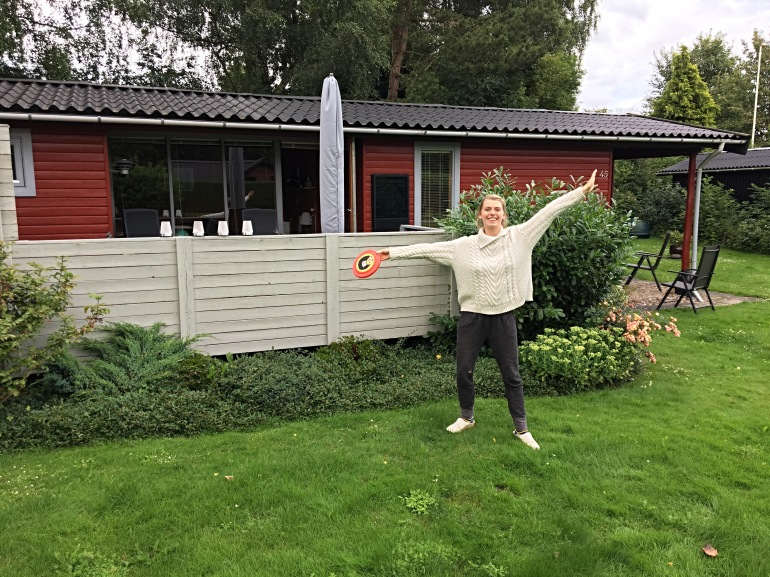 girl with frisbee in front of summer house in Denmark