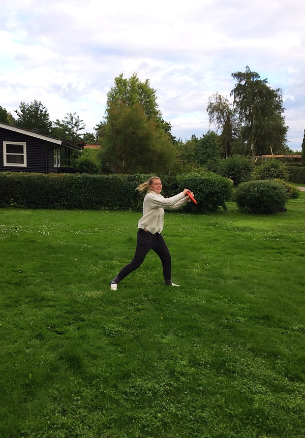 girl catches frisbee in yard game in Denmark