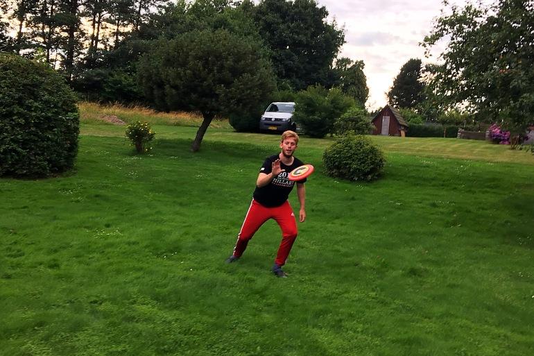 boy catches frisbee in yard game in denmark