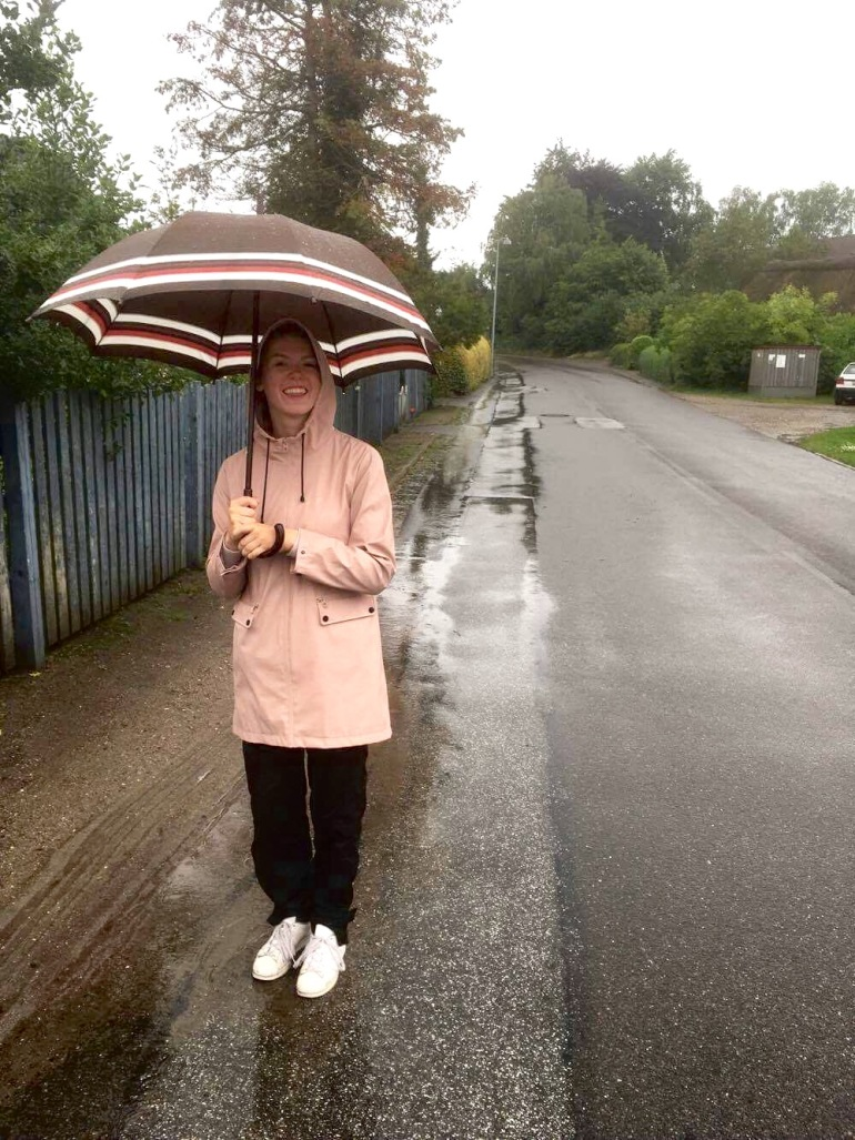 girl under umbrella on road on a rainy day