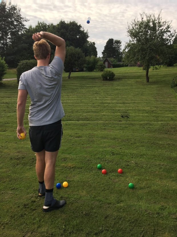 boy throws bocce ball in yard game