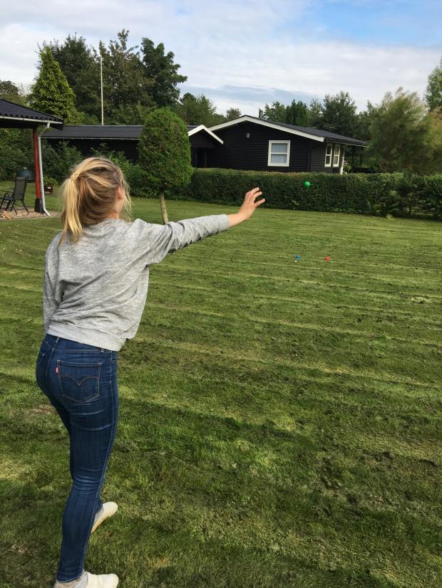 girl throws bocce ball in yard game
